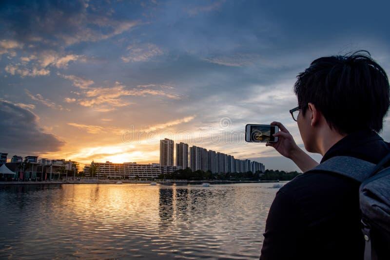Azjatycki mężczyzna bierze zmierzch fotografię na smartphone obraz stock