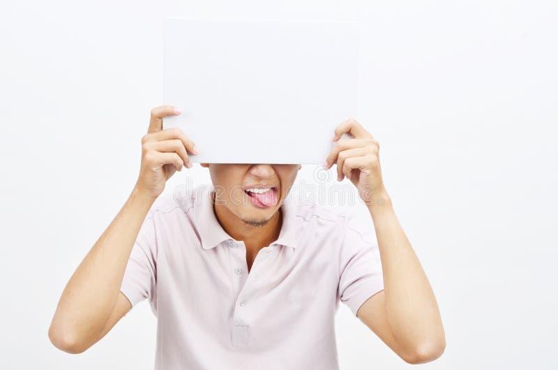 Azjatycki mężczyzna jęzor out trzyma białego papierowej karty nakrycie ono przygląda się zdjęcie royalty free