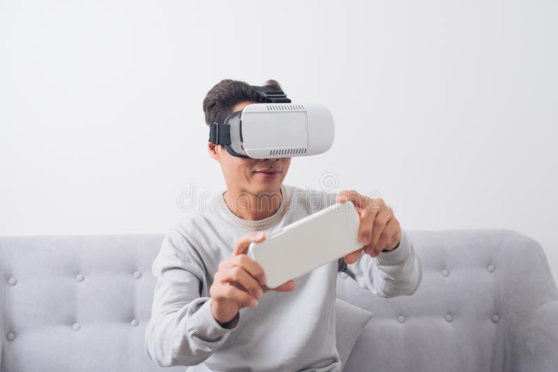Azjatycki mężczyzna jest ubranym rzeczywistość wirtualna gogle lub VR słuchawki obrazy royalty free