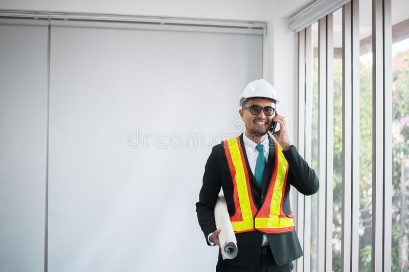 Azjatycki mężczyzna konstruuje używać telefon komórkowego i trzymający projekt w biurze zdjęcia stock