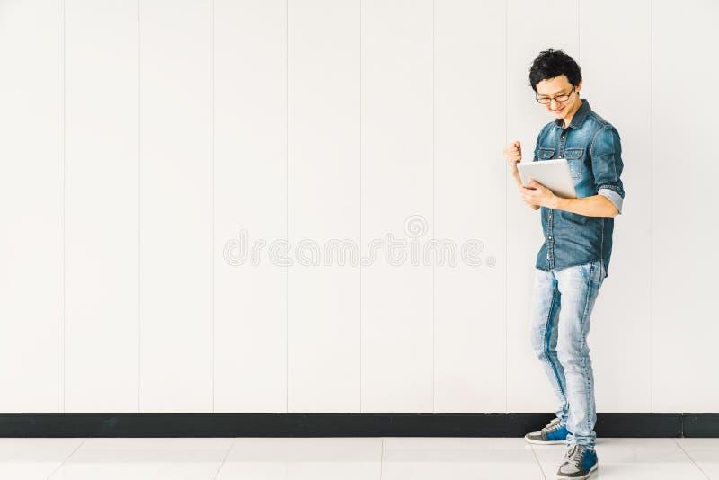Azjatycki mężczyzna lub student collegu używa cyfrowego pastylka doping świętujemy sukces, kopii przestrzeń na biel ściany tle obrazy royalty free