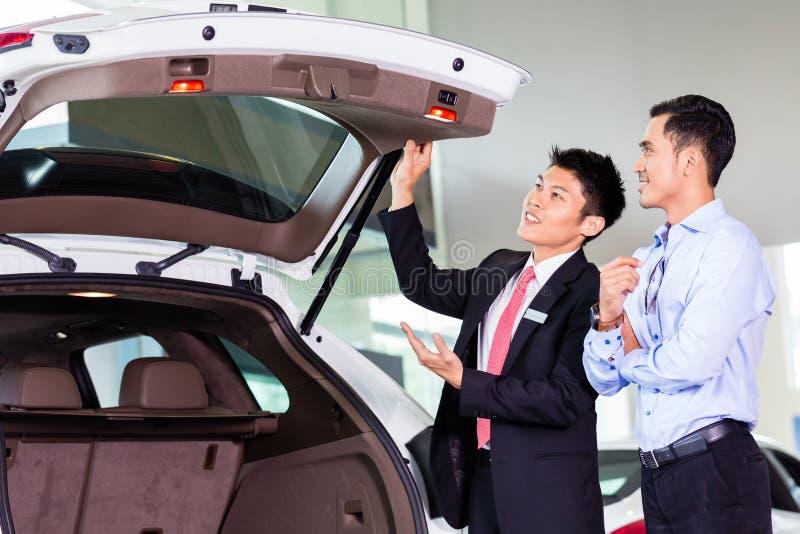 Azjatycki mężczyzna patrzeje samochód w przedstawicielstwie handlowym obrazy royalty free