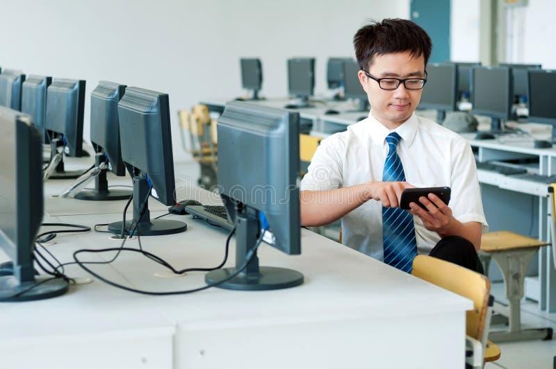 Azjatycki mężczyzna pracuje w komputerowym pokoju obraz stock