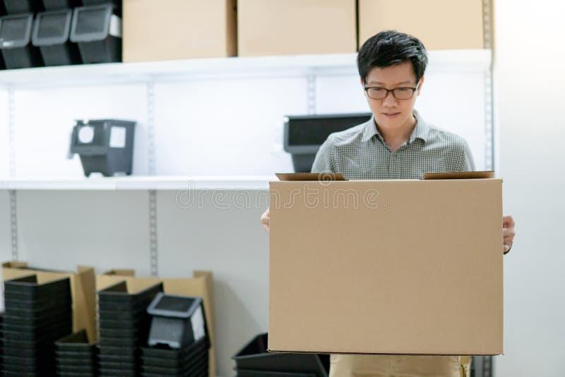 Azjatycki mężczyzna przewożenia pudełka zakupy w magazynie fotografia stock