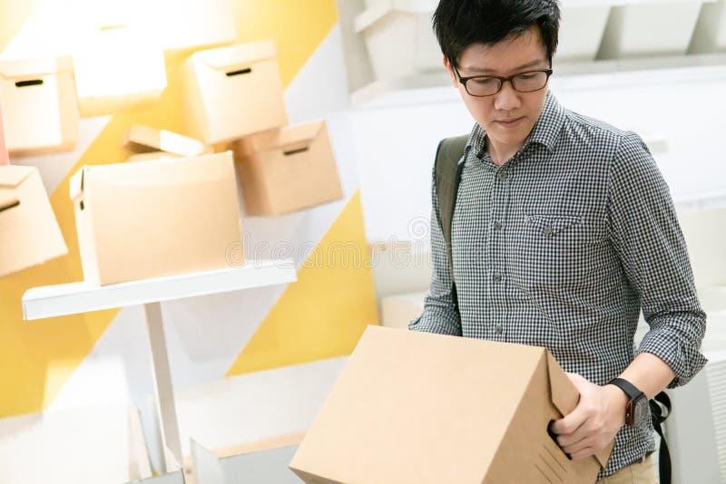 Azjatycki mężczyzna przewożenia pudełka zakupy w magazynie obrazy royalty free