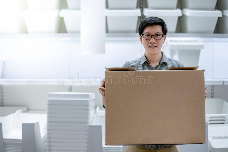 Azjatycki mężczyzna przewożenia pudełka zakupy w magazynie obraz royalty free