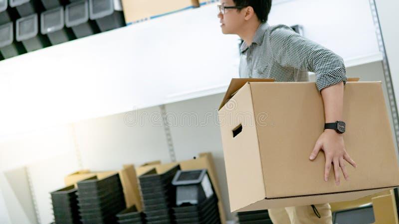 Azjatycki mężczyzna przewożenia pudełka zakupy w magazynie zdjęcie royalty free