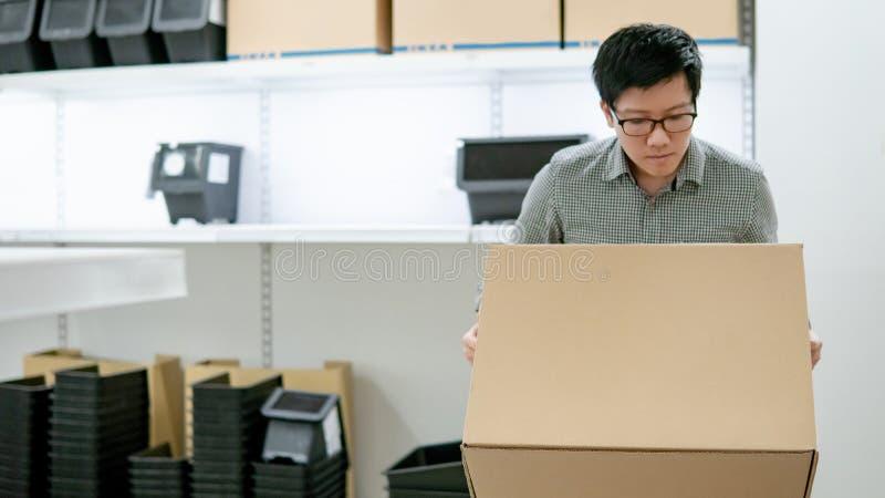 Azjatycki mężczyzna przewożenia pudełka zakupy w magazynie obraz stock