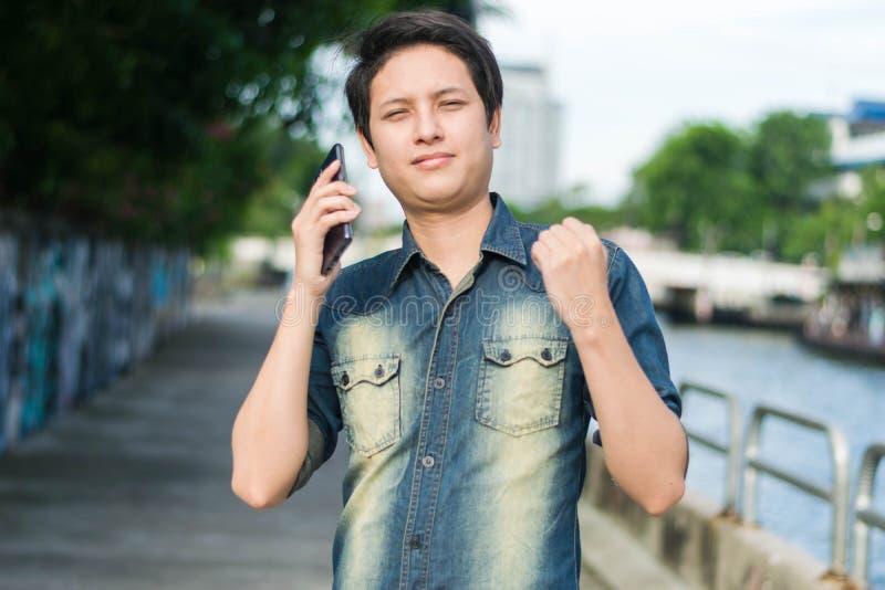 Azjatycki mężczyzna stoi jego ręki w górę i pokazuje zdjęcia stock