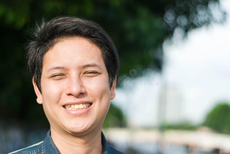 Azjatycki mężczyzna stoi jego szczęśliwy ono uśmiecha się i pokazuje obraz stock