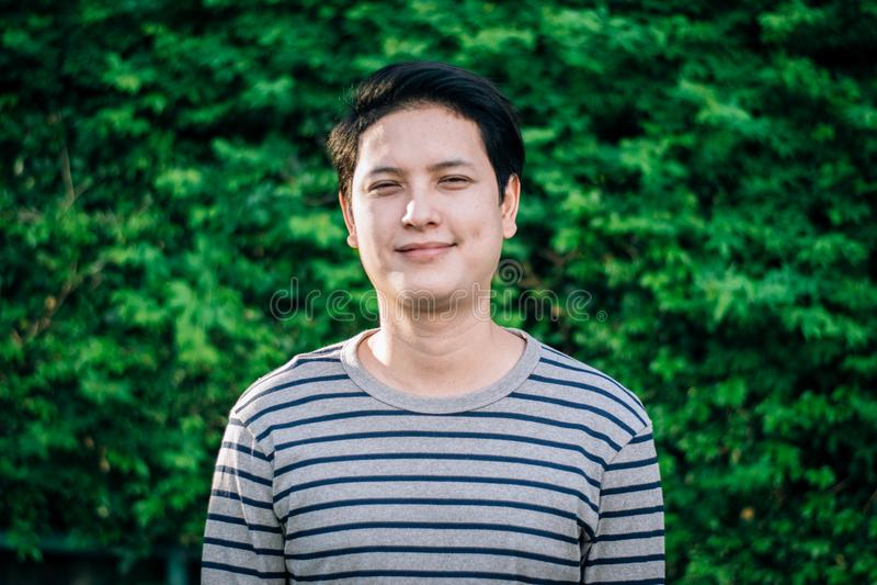 Azjatycki mężczyzna stoi jego szczęśliwy ono uśmiecha się i pokazuje zdjęcia royalty free