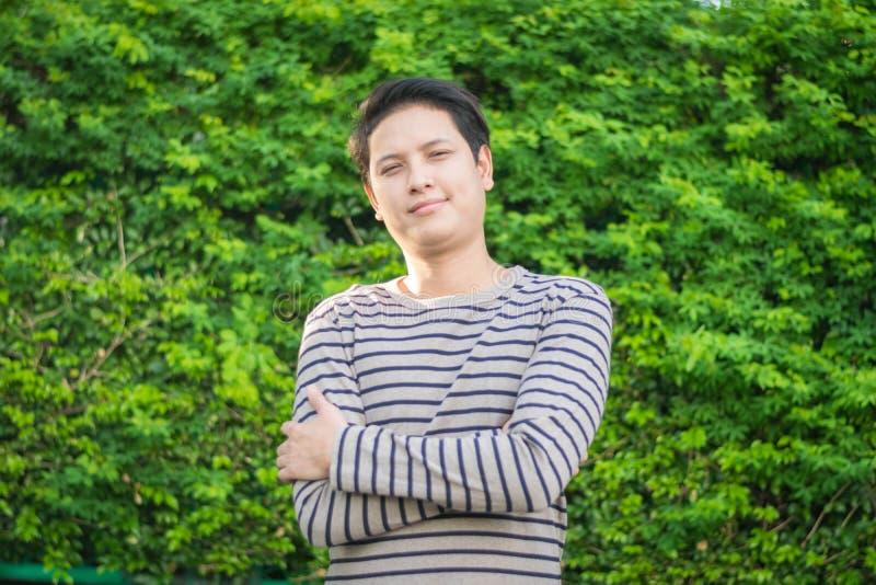 Azjatycki mężczyzna stoi jego szczęśliwy ono uśmiecha się i pokazuje zdjęcie stock