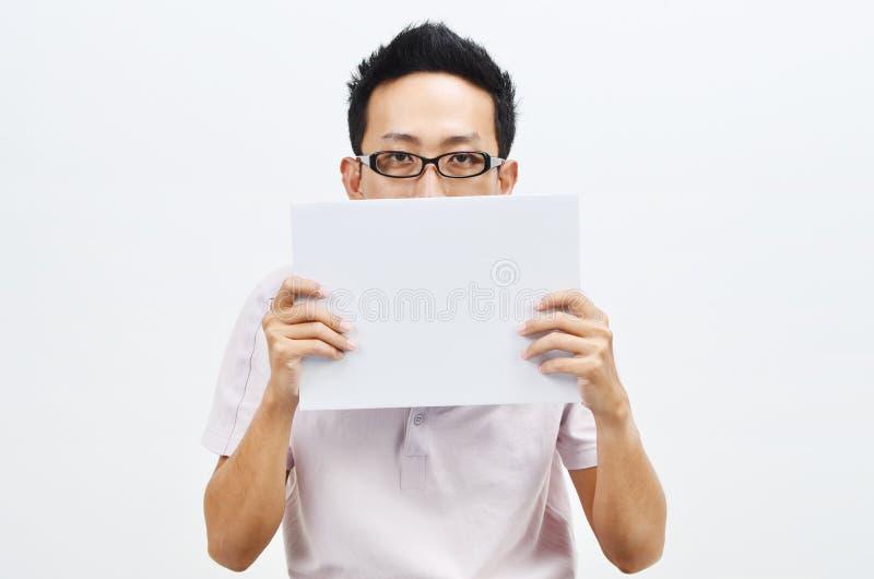 Azjatycki mężczyzna trzyma białą papierowej karty nakrycia twarz obrazy stock