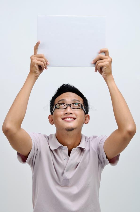 Azjatycki mężczyzna trzyma białą pustą kartę zdjęcia stock