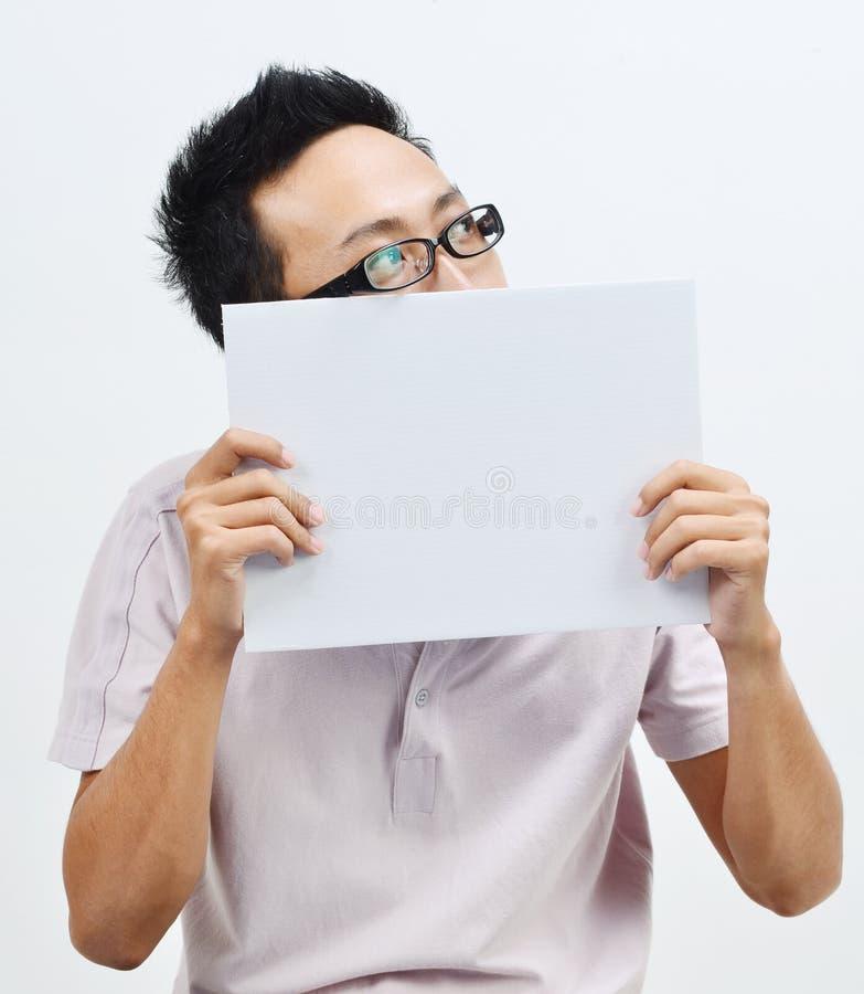 Azjatycki mężczyzna trzyma białego papierowej karty nakrywkowego usta fotografia stock