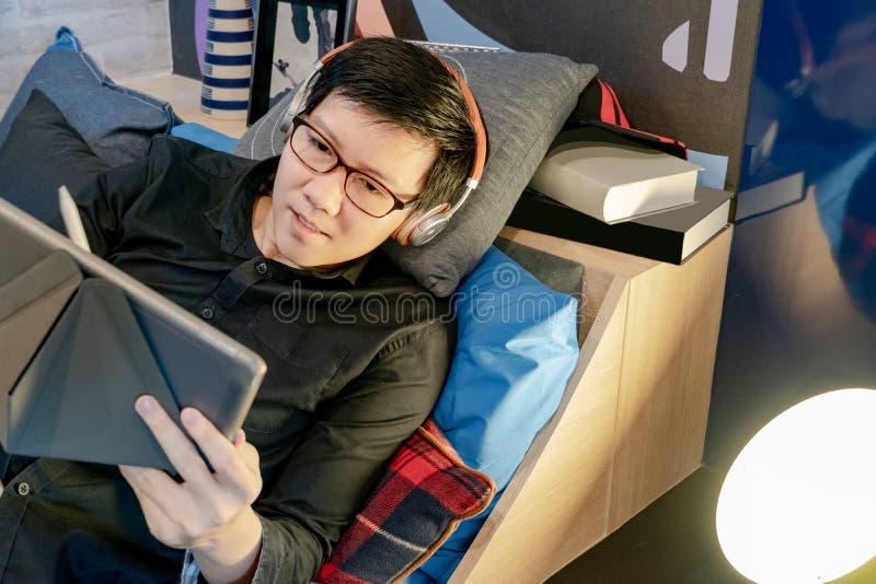 Azjatycki mężczyzna używa pastylkę na łóżku w sypialni obraz stock