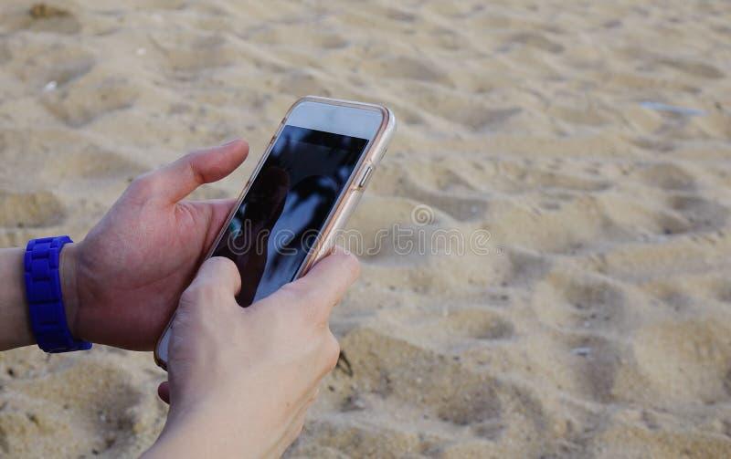 Azjatycki mężczyzna używa smartphone na plaży zdjęcie stock