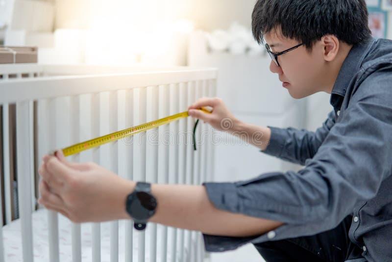 Azjatycki mężczyzna używa taśmy miarę na berbeci łóżkowych poręczach fotografia royalty free