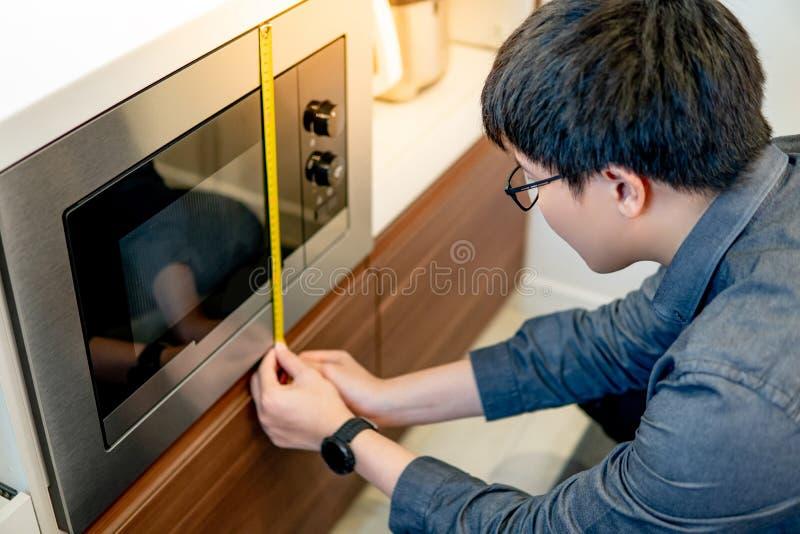 Azjatycki mężczyzna używa taśmy miarę na mikrofali zdjęcia royalty free