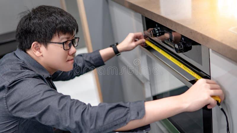 Azjatycki mężczyzna używa taśmy miarę na piekarniku fotografia stock