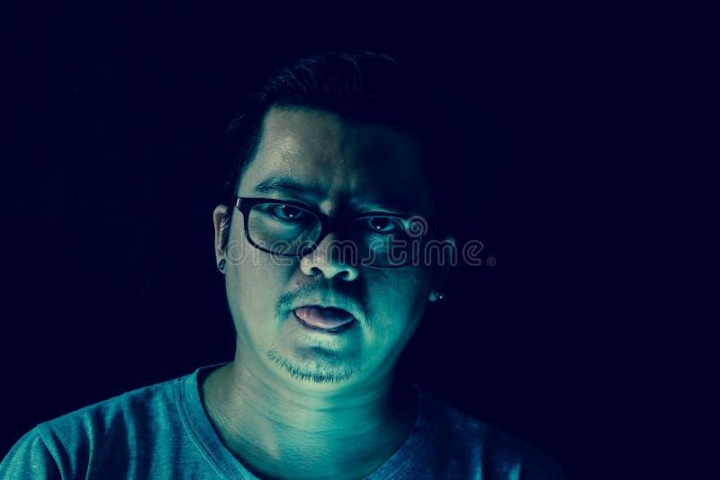 Azjatycki mężczyzna w zmroku Jego jęzor z jasnozielony strasznym śmieszny i fotografia stock