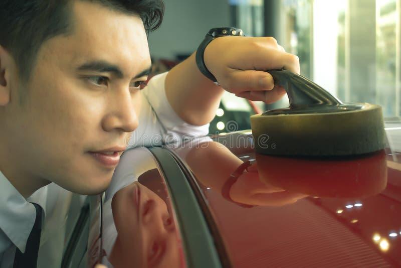 Azjatycki mężczyzna wipping samochód z DOWODZONYM reflektorem dla klientów zdjęcie royalty free
