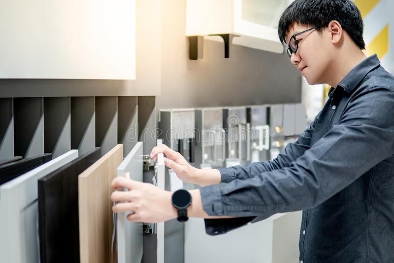 Azjatycki mężczyzna wybiera gabineta lub countertop materiały zdjęcia stock