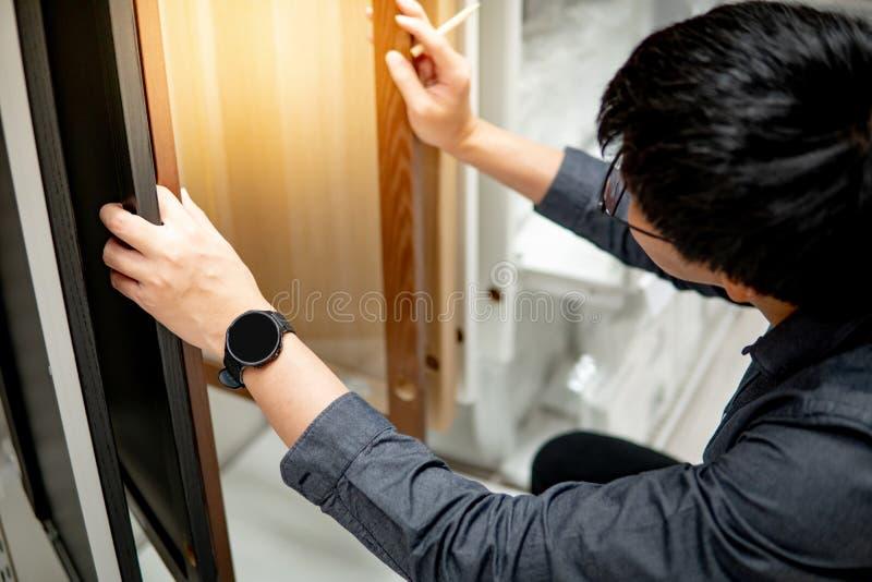 Azjatycki mężczyzna wybiera gabineta lub countertop materiały obrazy stock