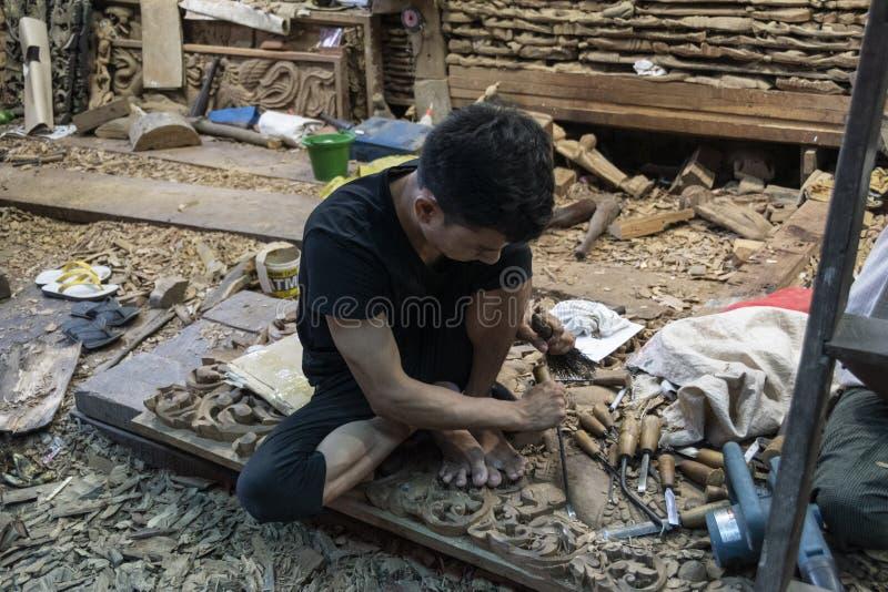Azjatycki mężczyzny cyzelowania drewno fotografia stock