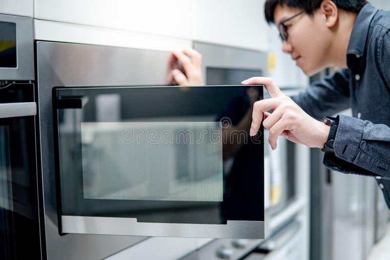 Azjatycki mężczyzny otwarcia mikrofali drzwi obrazy royalty free