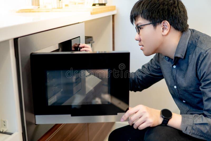Azjatycki mężczyzny otwarcia mikrofali drzwi obraz royalty free