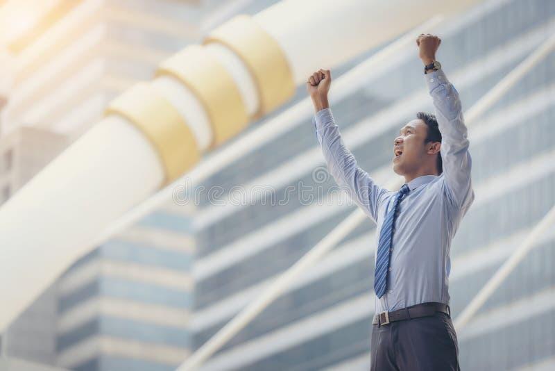 Azjatycki męski biznesowy mężczyzna podnosi jego ręki, rozgrymaszać w jego succes obraz royalty free