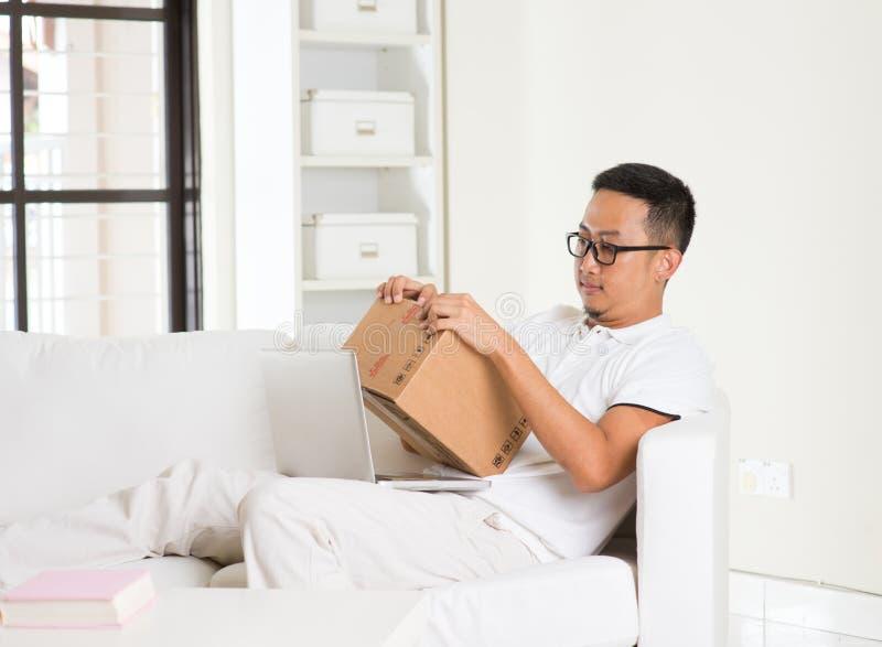 Azjatycki męski online zakupy z pakuneczkiem otrzymywającym zdjęcia stock