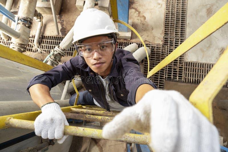 Azjatycki męski pracownik Jest ubranym zbawczego hełm wspina się drabinę obrazy stock