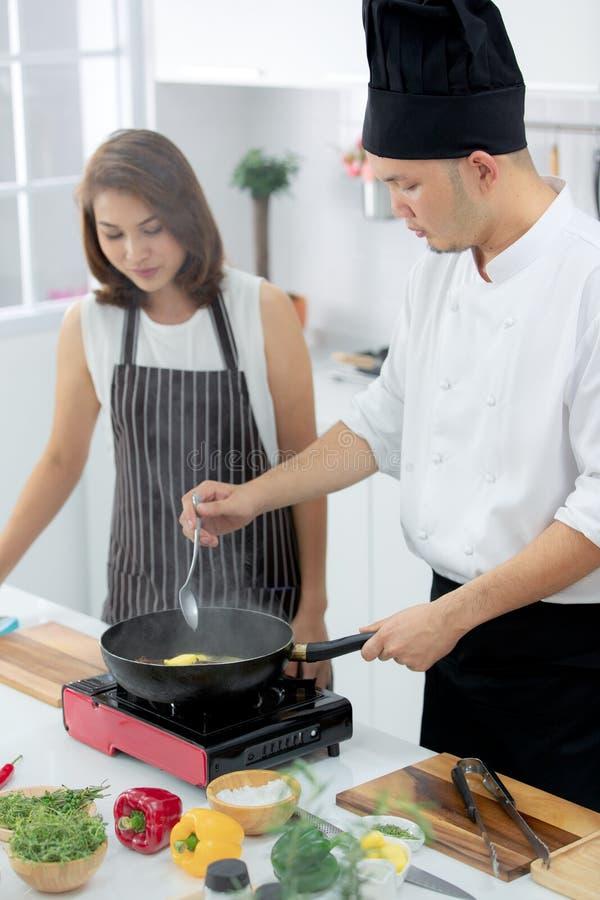 Azjatycki męski szef kuchni demonstruje dlaczego gotować dla pięknego ucznia obraz royalty free