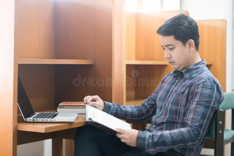 Azjatycki męski uczeń czyta książkę w bibliotece, zdjęcia stock
