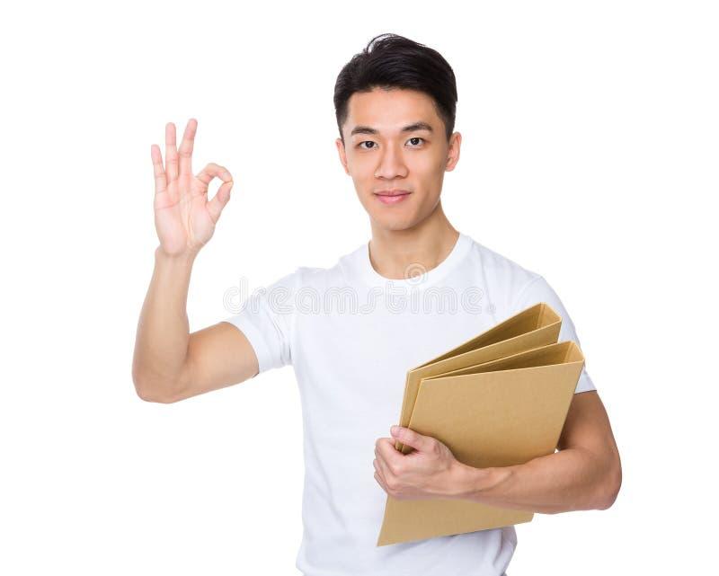 Azjatycki młodego człowieka chwyt z skoroszytowym i ok szyldowym gestem obraz stock