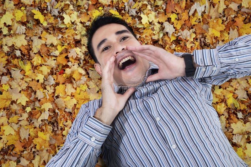 Azjatycki młody człowiek krzyczy na liściach zdjęcie stock