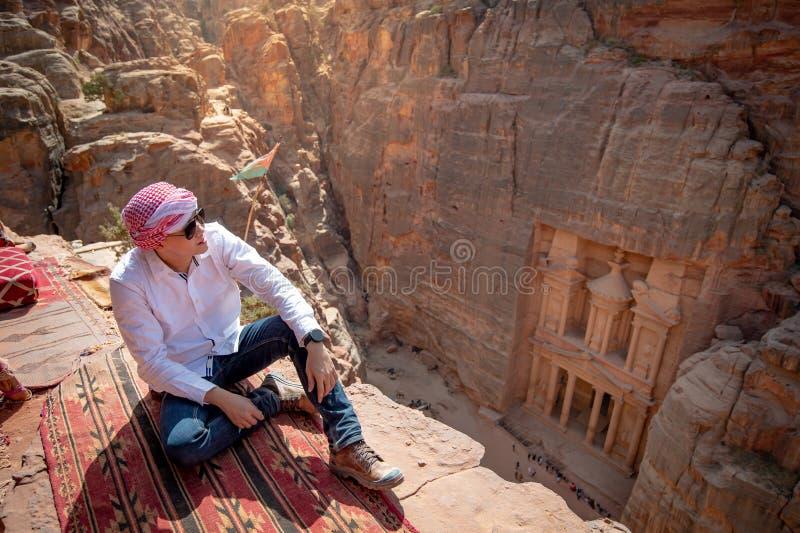 Azjatycki m??czyzny podr??nika obsiadanie w Petra, Jordania zdjęcie royalty free