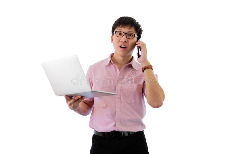 Azjatycki m?ody biznesmen pozycj?, mienie laptop dla pracowa? z ruchliwie na odosobnionym na wihte tle i telefon i obrazy royalty free