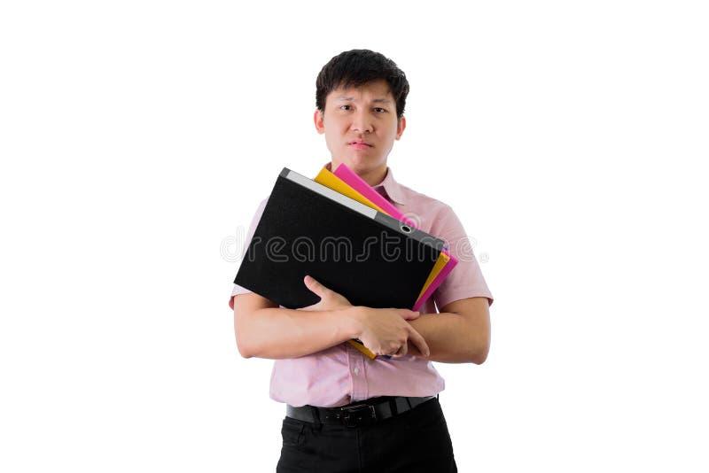Azjatycki m?ody biznesmen trwanie, ci??kiego dzia?anie z i wiele dokumentami na odosobnionym na wihte tle i falc?wkami obrazy stock