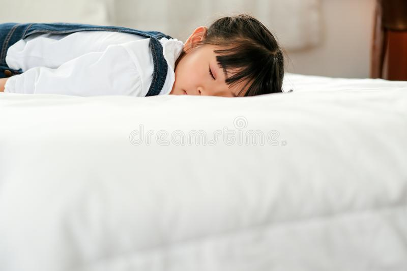 Azjatycki małej dziewczynki kłamstwo, sen na białym łóżku z warunkiem pokojowy i i relaksujemy czas fotografia royalty free