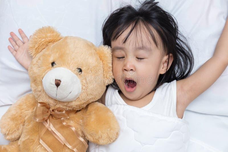 Azjatycki mały Chiński dziewczyny dosypianie z misiem zdjęcia royalty free