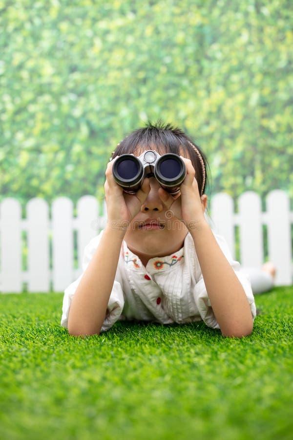 Azjatycki Mały Chiński dziewczyny klęczenie na trawie i bawić się z fotografia stock