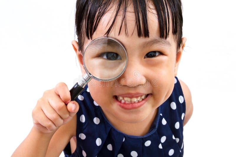 Azjatycki Mały Chiński dziewczyny mienia Powiększać - szkło obrazy royalty free