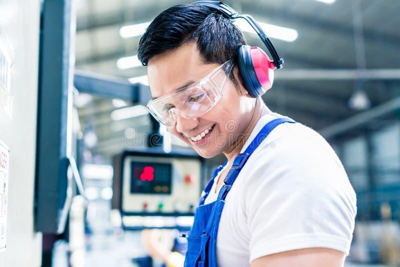 Azjatycki maszynowy operator w produkci roślinie zdjęcia royalty free