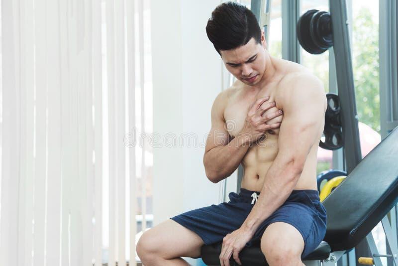 Azjatycki Mięśniowy mężczyzna ma ból na jego klatce piersiowej obraz royalty free