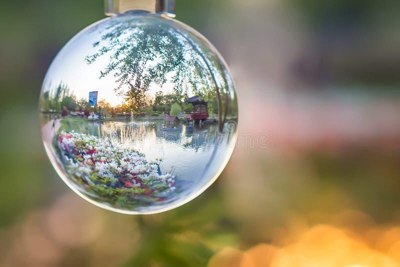 Azjatycki miasto park z jeziorem, okwitnięcie kwiatami i pawilonem widzieć przez krystalicznej szklanej piłki, horyzontalnej zdjęcia stock
