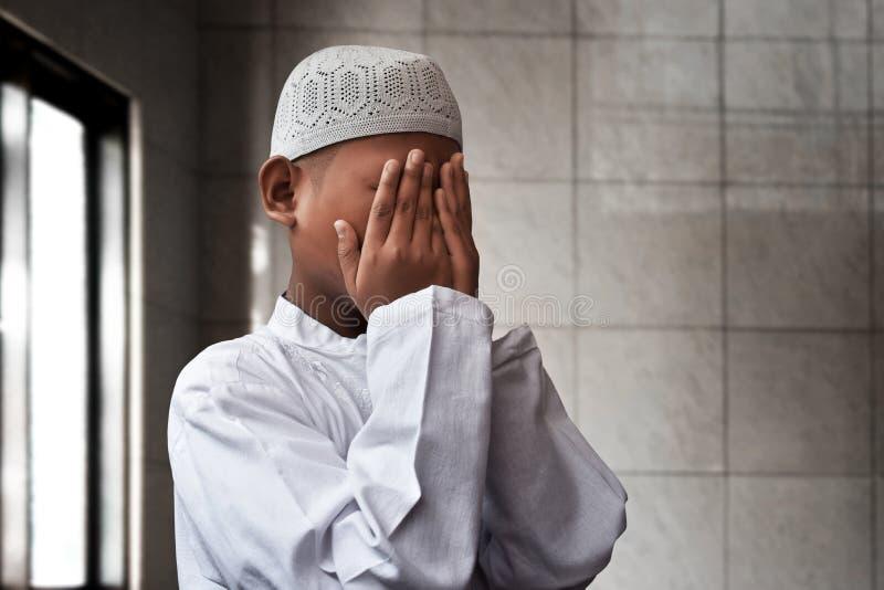 Azjatycki muzułmański dzieciaka modlenie wśrodku meczetu obrazy royalty free