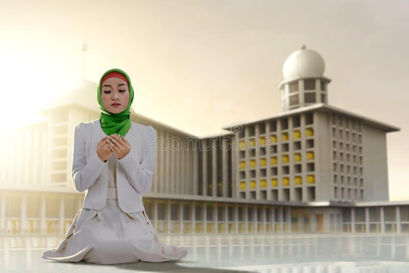 Azjatycki Muzułmański kobiety obsiadanie wewnątrz modli się pozycję podczas gdy nastroszone ręki i ono modli się obrazy stock
